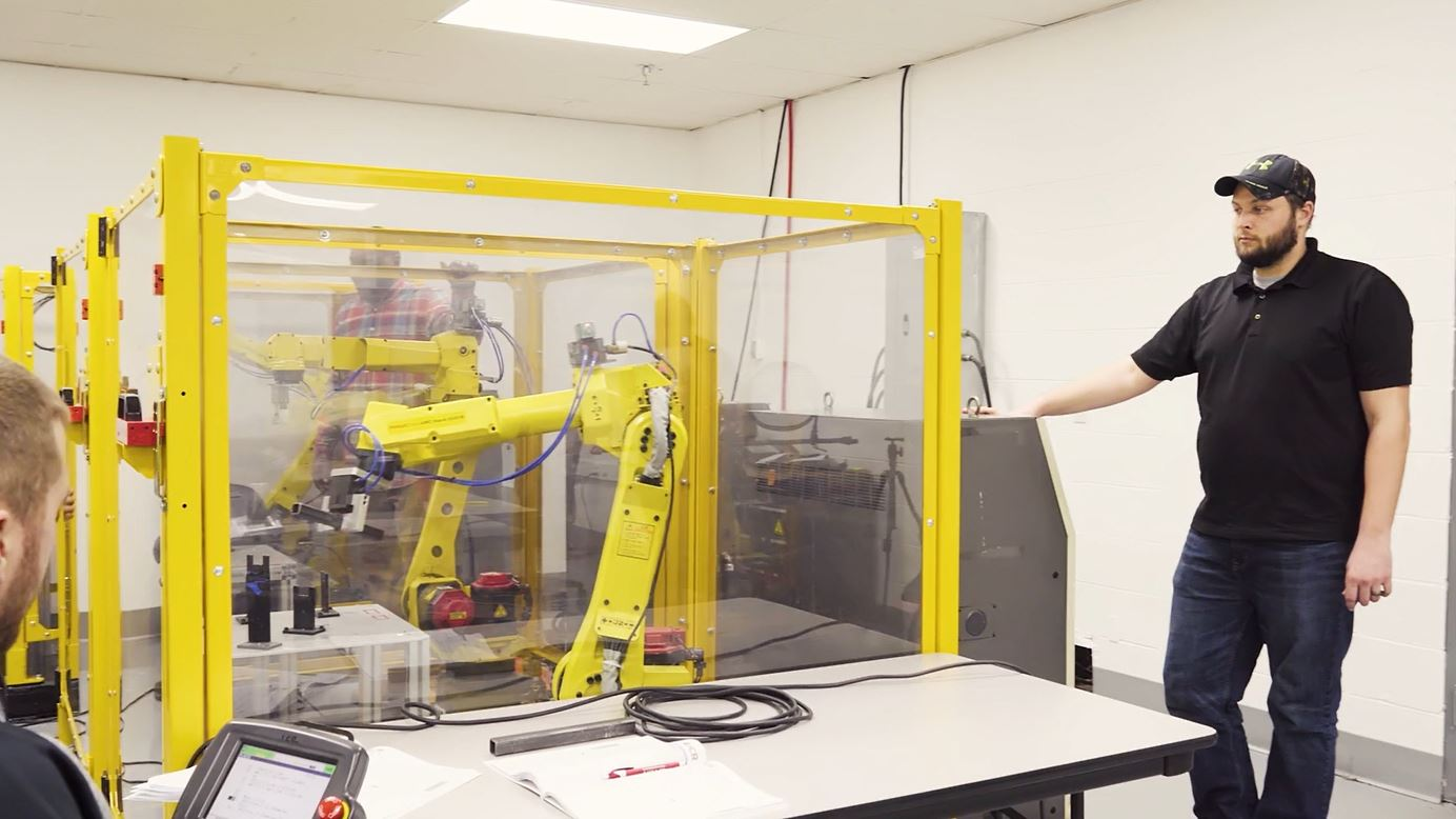 Fanuc Robot Training Classroom with Student Holding a Teach Pendant