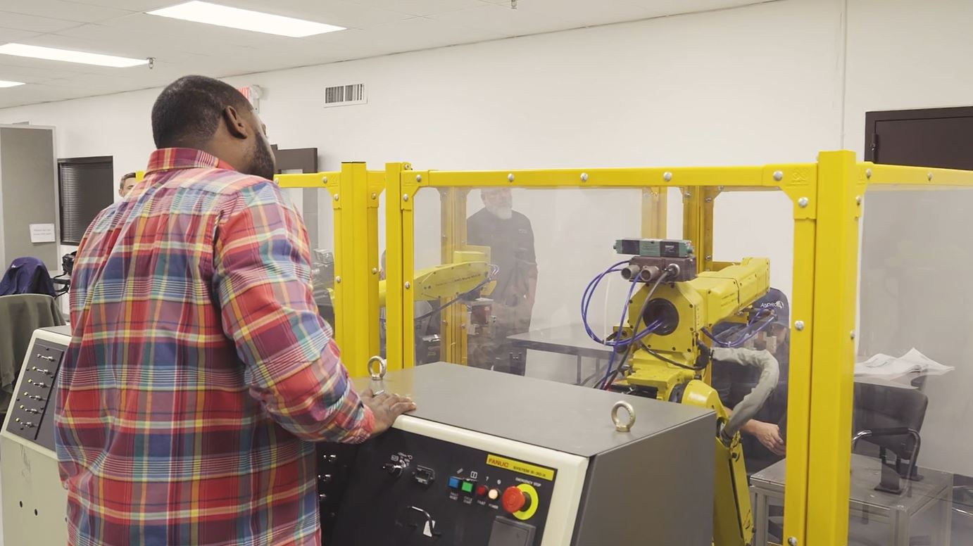 Student Standing Next to Fanuc R-30iA Robot Controller